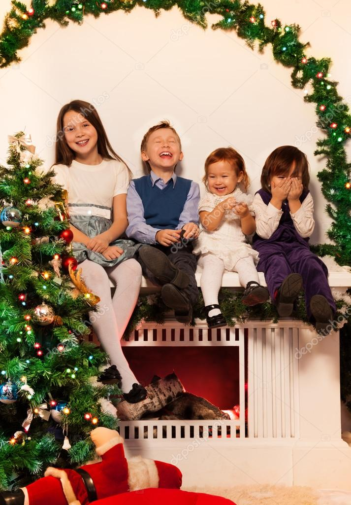 Four kids sitting on the fire place with Christmas tree close to them — Stock Photo #16295343