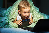 Playing videogames hiding in bed — Stock Photo