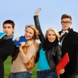 Four students with books cheering — Stock Photo #22245665