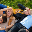 Royalty-Free Stock Photo: Group of four young people laying in the grass