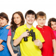 Smiling boy with binoculars in a group — Stock Photo
