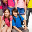 Stock Photo: Couple kids sitting among friends