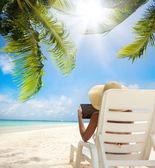 Rilassarsi sulla spiaggia e tablet computer — Foto Stock