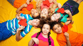 Group of kids laying with red hearts — Stock Photo