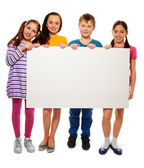 Four kids showing board with advertising — Stock Photo