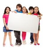 Group of schoolchildren holding white board — Stock Photo
