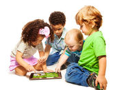 Four little kids playing tablet — Stock Photo