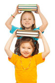 Smart girls with pile of books — Stock Photo