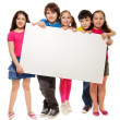 Group of schoolchildren holding white board — Stockfoto