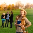 Beautiful blond student with friends — Stock Photo #24688849