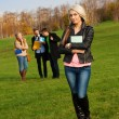 Female student and her friends on background — Stock Photo