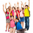 Group of happy kids lifting hands — Stock Photo