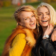 Two young women laughing in the park — Stock Photo