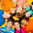 Group of happy kids laying in circle — Stock Photo #24689753