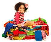Black girl sitting in the basket with clothes — Stock Photo