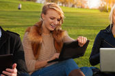 Blond student with laptop laughing — Stock Photo