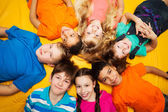 Group of happy kids laying in circle — Stock Photo