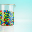 Glass full of color pills — Stock Photo #28469121