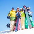 Stock Photo: Four happy friends hug and hold snowboards