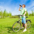 Young man on a bike drinking water — Stock Photo #28478829