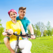 Smiling couple on the bike — Stock Photo