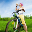 Young woman on a bike drinking water — Stock Photo #28479447