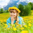 Beautiful little girl in dandelions — Stock Photo