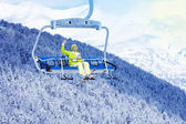 Happy skier in on the ski lift waiving hand — Stock Photo