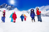 Group of kids walking in snow — Stock Photo