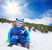 Junge sitzt im schnee auf schlitten — Stockfoto