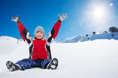 Happy boy sitting on sled on sunny day — Stock Photo