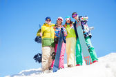 Four happy friends hug and hold snowboards — Stockfoto
