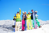 Four happy friends with snowboards — Stock Photo