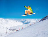 Cute snowboarder man jumping on ski resort — Stock Photo