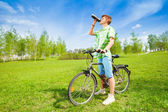 Young man on a bike drinking water — Stock Photo