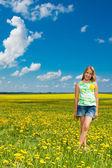 Chica en el campo del diente de león — Foto de Stock