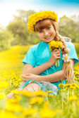 Blond girl in dandelions — Stock Photo