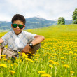 Stock Photo: Happy little black sitting boy in sunglasses