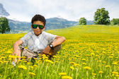 Happy little black sitting boy in sunglasses — Stock Photo