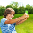 Boy taking picture with cell phone — Stock Photo #32010193