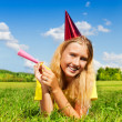 Blond girl lay with noisemaker — Stock Photo