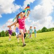 Beautiful girl run with kite together with friends — Stock Photo