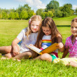 Three sisters read book in the park — Stock Photo