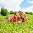 Two girls in the grass with butterfly — Stock Photo