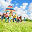 Little girl with friends and kite — Stock Photo