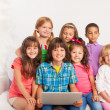 Smiling group of kids with laptop — Stock Photo