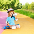 Boy rollerblading and drink water from bottle — Stock Photo