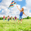 Girl running with kite with friends — Stock Photo