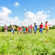 Large group of kids running in the park — Stock Photo