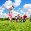 Cute girl with kite run with friends — Stock Photo